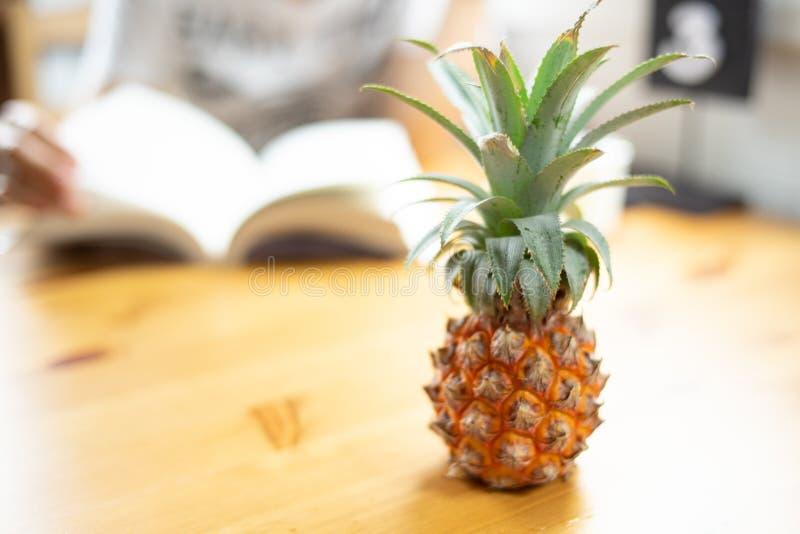 Composizione con il piccolo ananas delizioso sulla linguetta di legno della spiaggia immagine stock libera da diritti