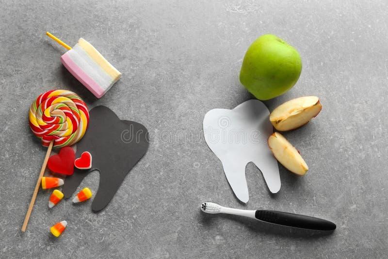 Composizione con l'alimento sano e non sano molare dei denti, su fondo grigio immagine stock libera da diritti