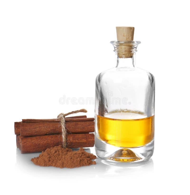 Composizione con l'olio di cannella essenziale in bottiglia di vetro fotografie stock libere da diritti