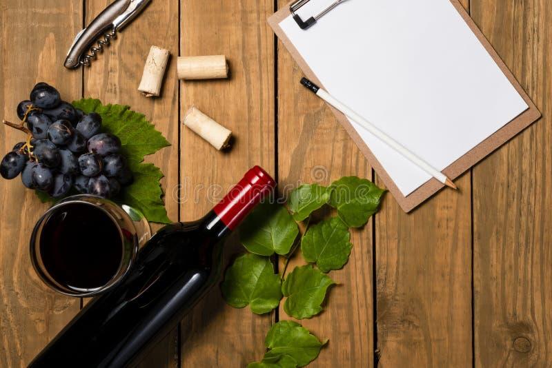 Composizione con la bottiglia e bicchiere di vino con il mazzo dell'uva e foglie di vite e blocco note su fondo di legno Vista su immagine stock