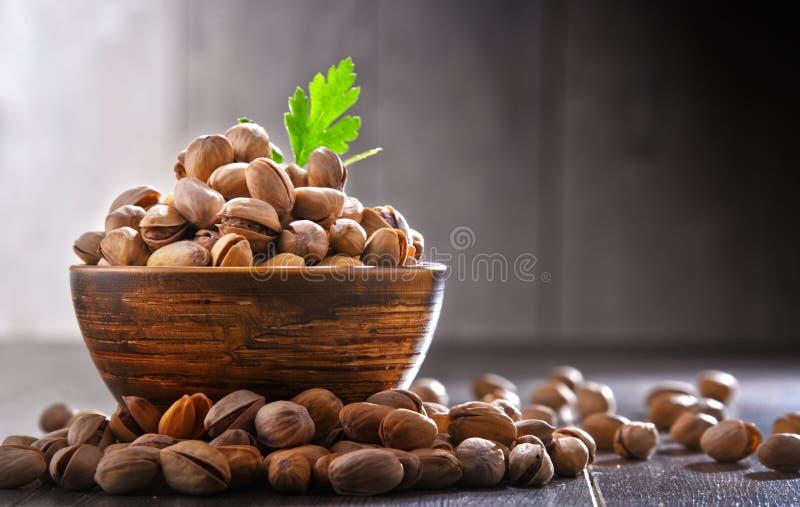 Composizione con la ciotola di pistacchio sulla tavola di legno squisitezze fotografia stock