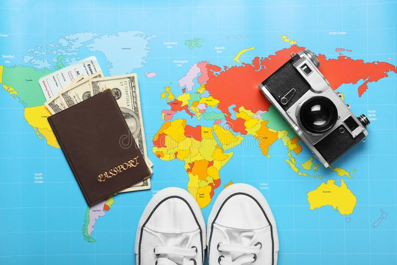 Composizione con la macchina fotografica, i gumshoes ed il passaporto della foto sulla mappa di mondo Concetto di pianificazione  immagine stock