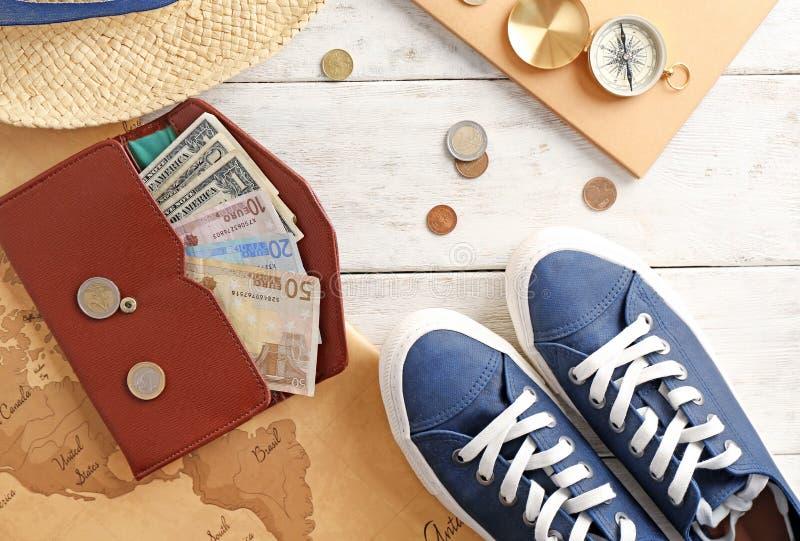 Composizione con la mappa delle scarpe, dei soldi, della bussola e di mondo su fondo di legno concetto di corsa fotografia stock