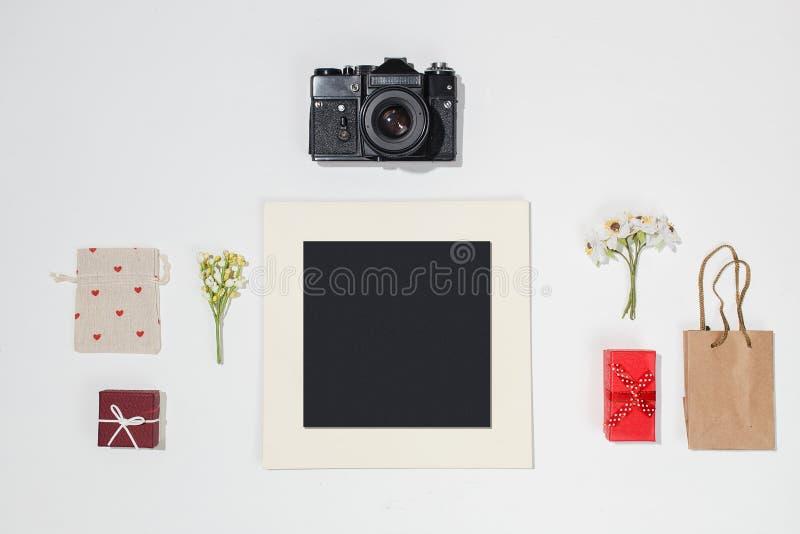 Composizione con la struttura nera della foto, la retro macchina fotografica, i contenitori di regalo rossi, la borsa del mestier fotografia stock