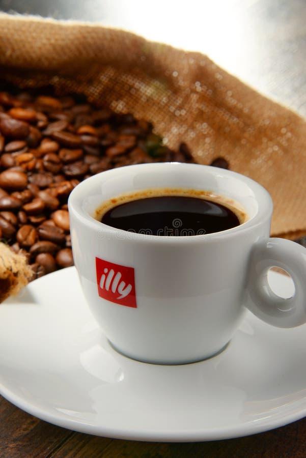 Composizione con la tazza del caffè e dei fagioli di Illy fotografia stock libera da diritti