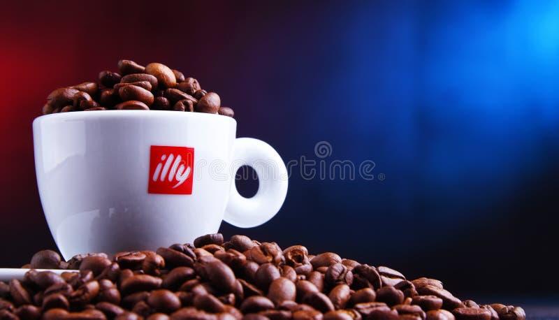 Composizione con la tazza del caffè e dei fagioli di Illy fotografia stock