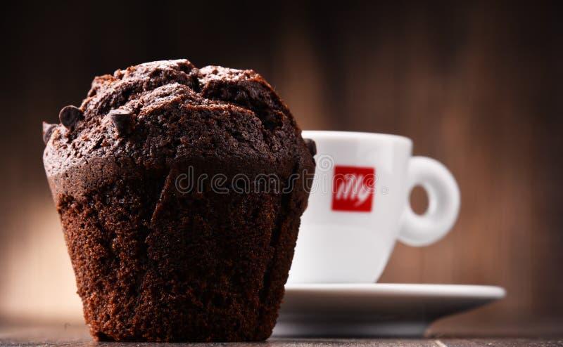 Composizione con la tazza del caffè e del muffin di Illy fotografia stock libera da diritti