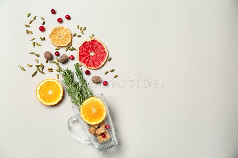 Composizione con la tazza e gli ingredienti per vin brulé saporito su fondo bianco fotografia stock libera da diritti