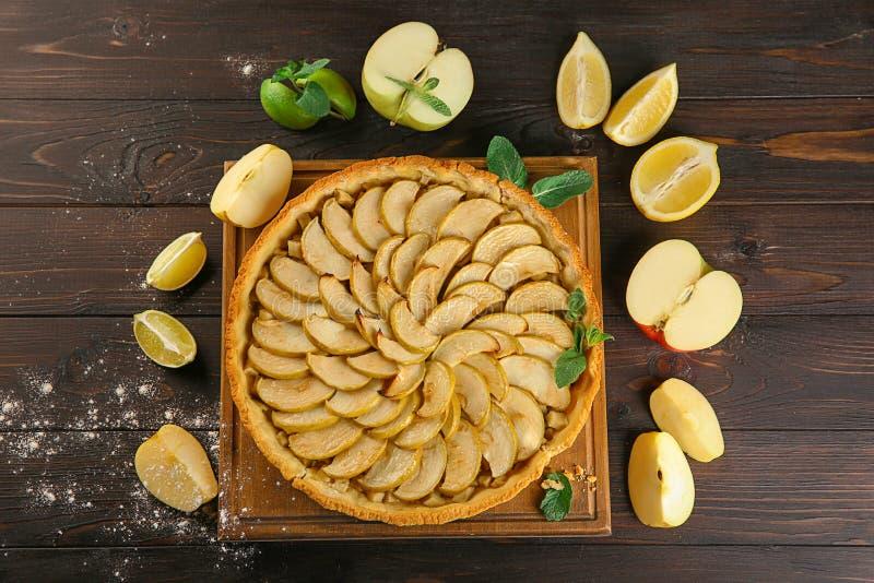 Composizione con la torta di mele casalinga saporita e frutti su fondo di legno immagini stock libere da diritti