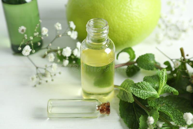 Composizione con le bottiglie degli oli essenziali dell'agrume sulla tavola immagini stock libere da diritti
