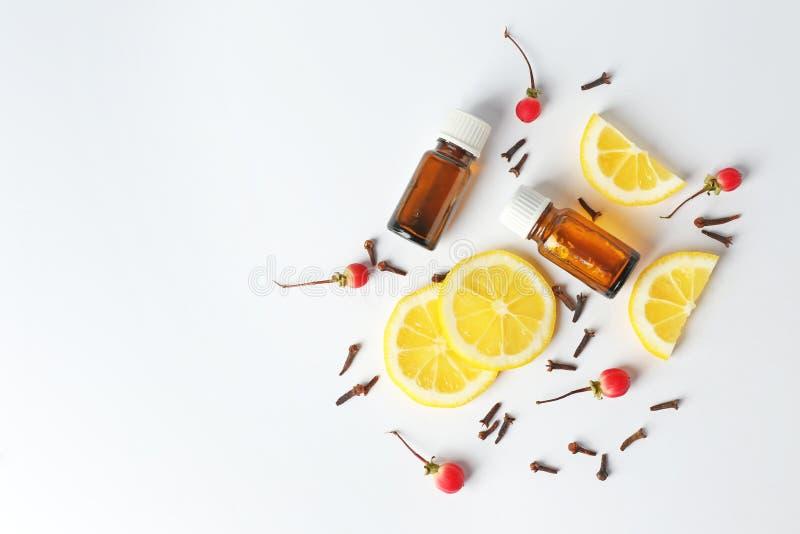 Composizione con le bottiglie di petrolio essenziale e del limone affettato su fondo bianco Estetiche naturali immagine stock