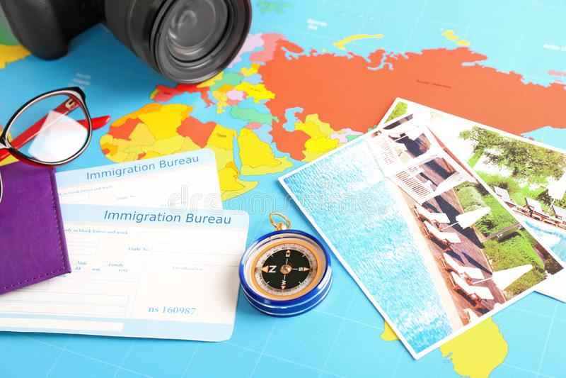Composizione con le carte dell'ufficio di immigrazione e della bussola sulla mappa di mondo Concetto di pianificazione di viaggio fotografia stock libera da diritti