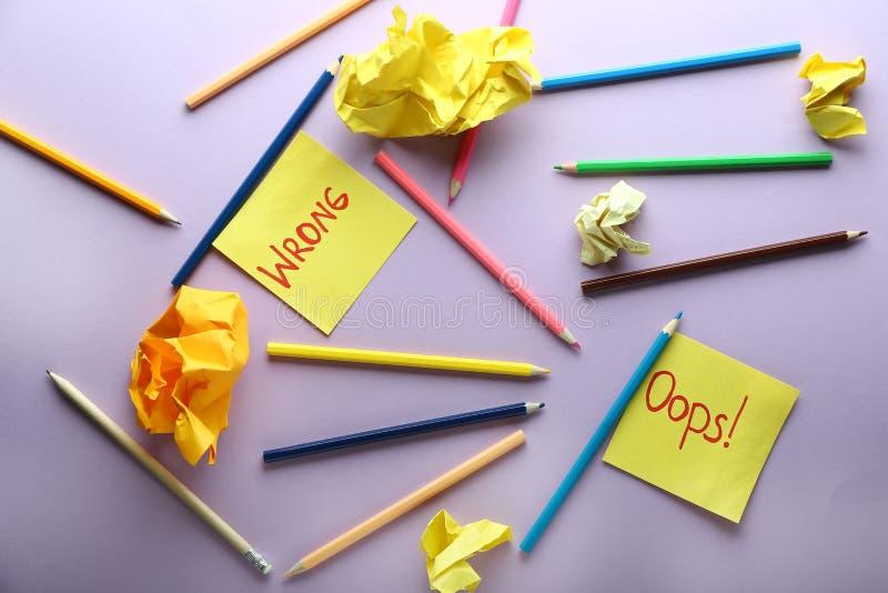 Composizione con le matite e le carte sgualcite sul fondo di colore Concetto di errore fotografia stock