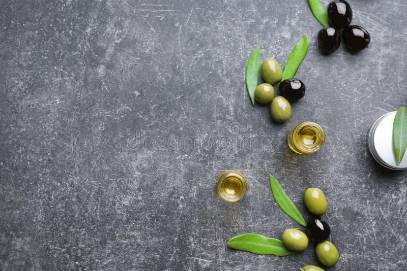 Composizione con olio d'oliva ed i cosmetici sulla tavola immagine stock