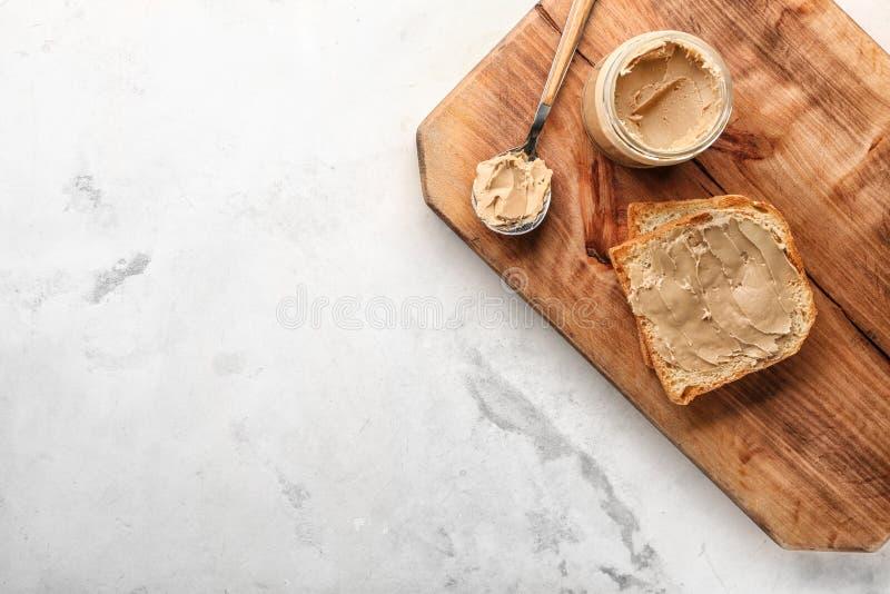 Composizione con pane tostato e burro di arachidi saporiti sulla tavola leggera immagine stock