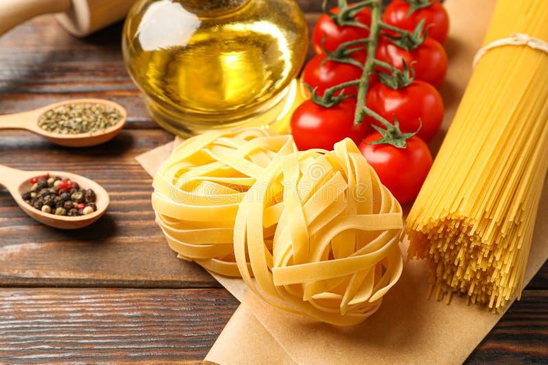 Composizione con pasta, i pomodori, il matterello, le spezie e l'olio d'oliva su fondo di legno, spazio per testo fotografie stock libere da diritti