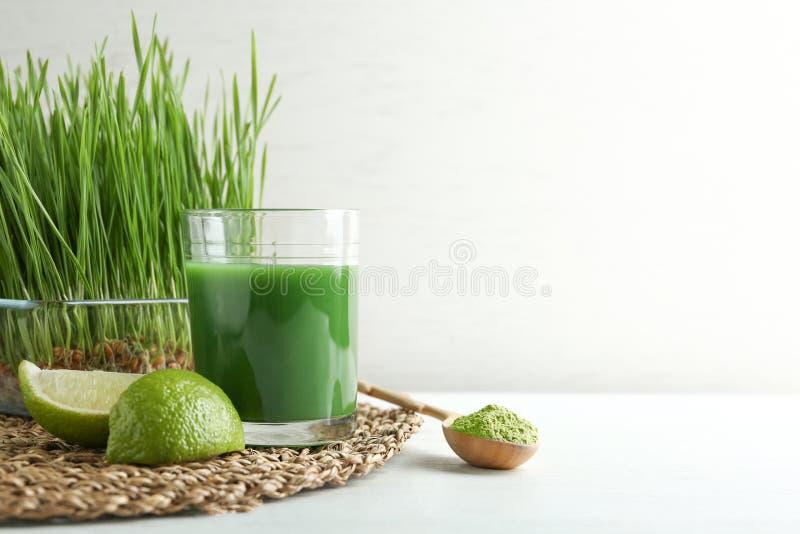 Composizione con vetro del succo e della calce dell'erba del grano sulla tavola contro fondo leggero fotografie stock libere da diritti