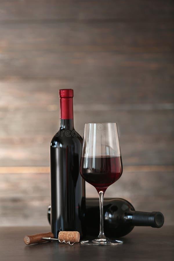 Composizione con vetro e le bottiglie di vino rosso sulla tavola immagine stock