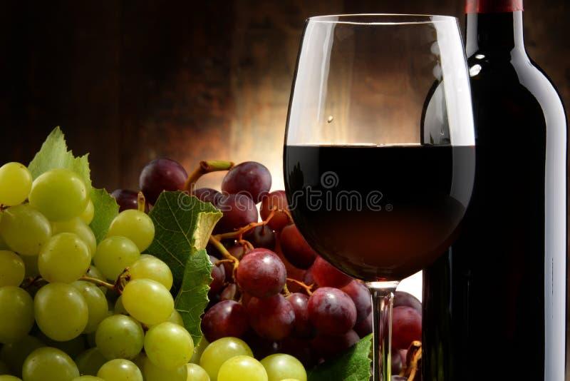 Composizione con vetro, la bottiglia di vino rosso e l'uva fresca immagini stock libere da diritti