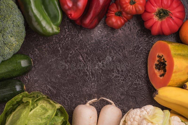 Composizione creativa fatta della frutta e delle verdure nei colori dell'arcobaleno su fondo di pietra, disposizione piana immagini stock libere da diritti