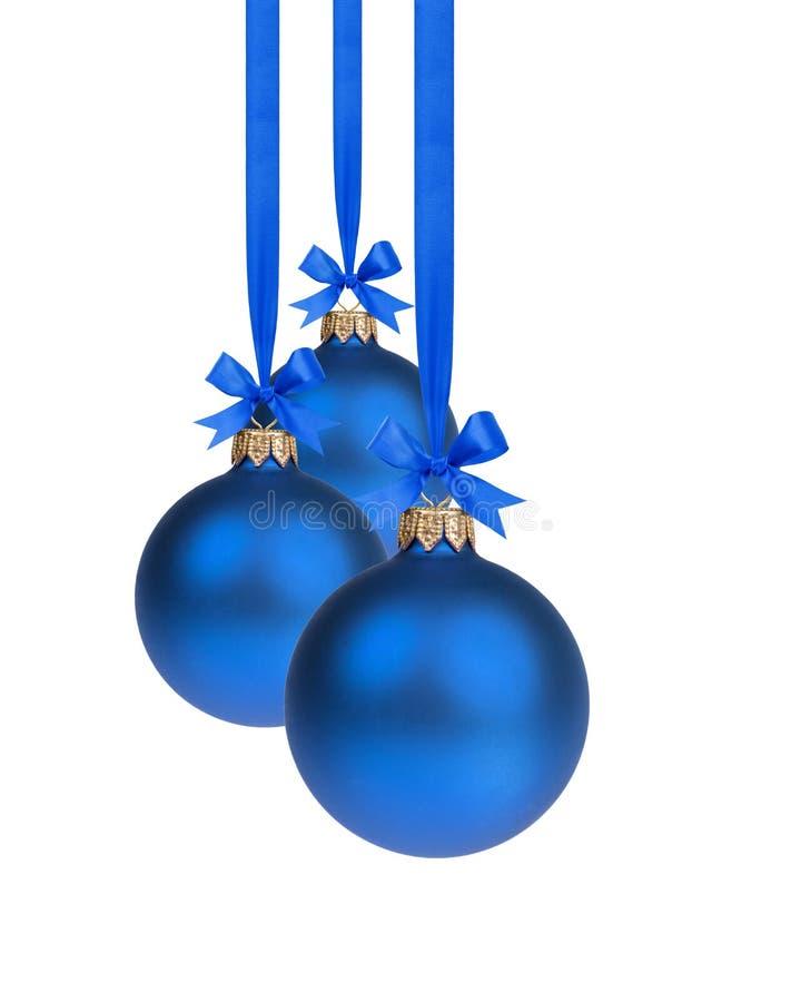Composizione da tre palle blu di natale che appendono sul nastro fotografie stock libere da diritti