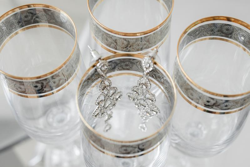 Composizione degli orecchini della sposa sui vetri alla moda d'annata fotografie stock