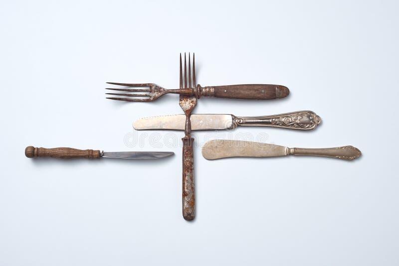 Composizione dei coltelli d'annata del metallo con un ornamento e di vecchie forcelle con le maniglie di legno su un fondo grigio fotografie stock