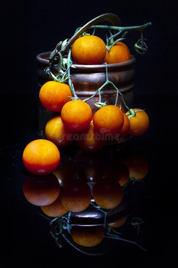 Composizione dei pomodori ciliegia e dei vasi di rame fotografie stock