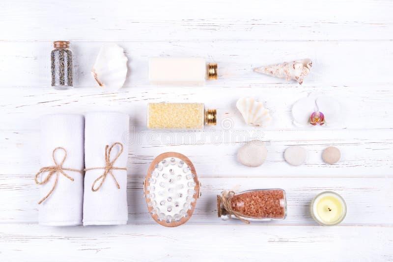Composizione dei prodotti differenti della stazione termale, di bellezza e di benessere su fondo di legno bianco fotografie stock