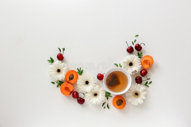 Composizione del cerchio dei fiori e dei frutti con una tazza di tè con la bustina di tè di forma del cuore fotografie stock libere da diritti