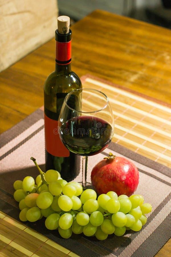 Composizione del melograno, dell'uva di moscato gialla, del vetro e della bottiglia di vino rosso su un bordo di legno fotografia stock