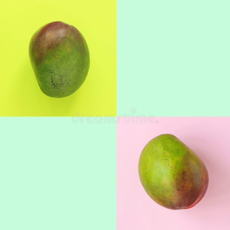 Composizione del modello di un verde saporito dolce e di un mango rosso che si trovano su un fondo rosa, giallo e della menta, im fotografia stock libera da diritti