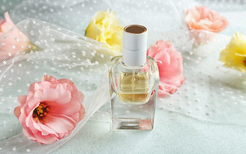 Composizione della bottiglia e dei fiori di profumo su fondo leggero immagini stock libere da diritti