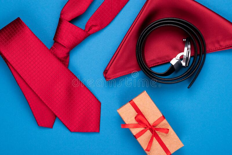 Composizione della cravatta del collo rosso, del quadrato tascabile, della scatola regalo e della cintura di cuoio su fondo ciano immagini stock