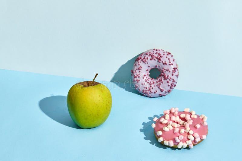 Composizione della frutta fresca e dolci, due guarnizioni di gomma piuma e mela verde fotografia stock libera da diritti