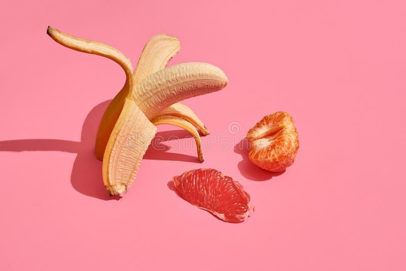 Composizione della frutta fresca, intera banana saporita fresca senza pelle, fetta di pompelmo e mandarino su fondo rosa fotografia stock