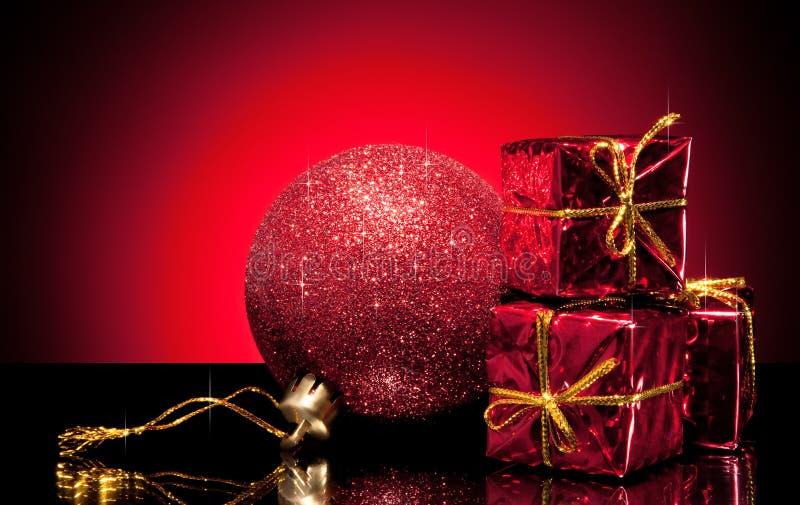 Composizione della sfera rossa e di piccoli contenitori di regalo fotografia stock libera da diritti