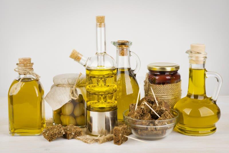 Composizione delle bottiglie di olio d'oliva e del pane nero sulla tavola immagini stock libere da diritti