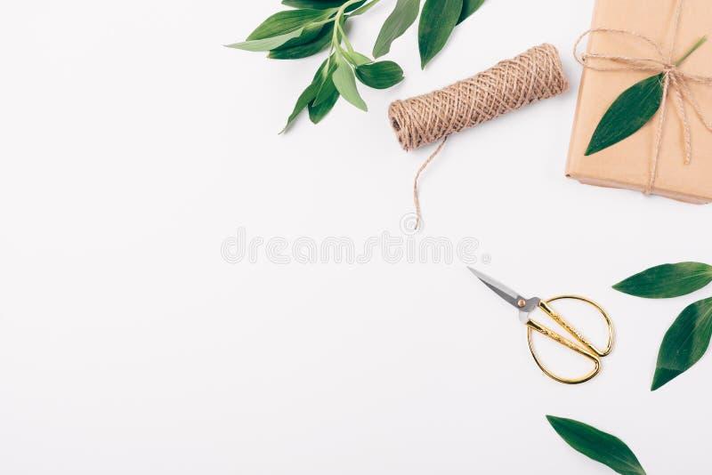 Composizione delle foglie verdi e del regalo imballato fatto a mano, vista superiore Struttura posta piana del lato decorativo di immagini stock