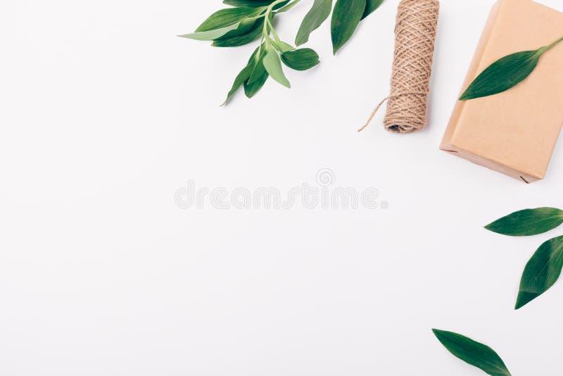 Composizione delle foglie verdi naturali e del regalo che imballano con il posto vuoto per testo o progettazione, vista superiore fotografia stock libera da diritti