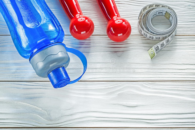 Composizione delle muto-campane rosse della bottiglia di acqua di misura di nastro su woode immagini stock libere da diritti