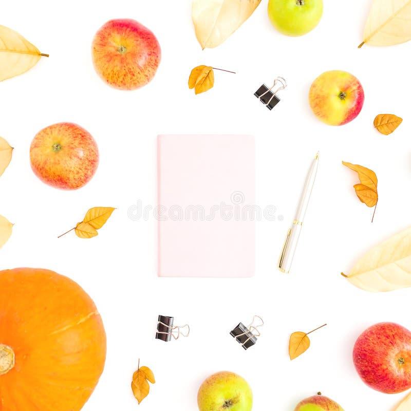 Composizione di autunno delle foglie di caduta, della frutta della mela e della zucca con il taccuino, la penna e le clip su fond fotografia stock libera da diritti