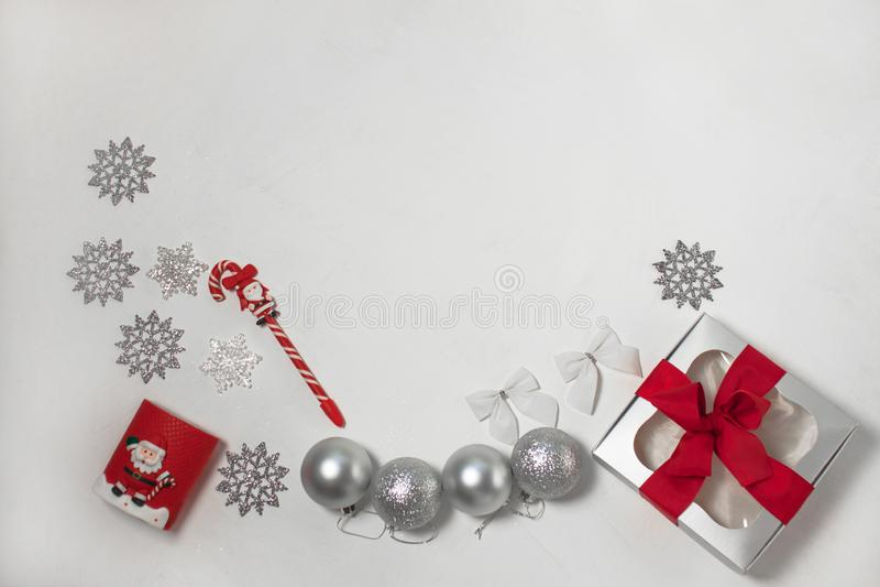Composizione di Natale delle decorazioni rosse e d'argento, contenitore di regalo con l'arco del nastro, flatlay immagine stock