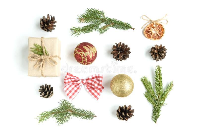 Composizione di Natale delle palle di Natale, del contenitore di regalo, dei coni e dei rami dell'abete isolati su fondo bianco immagine stock
