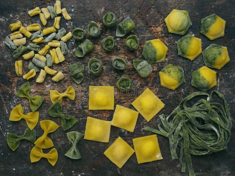 Composizione di pasta, dei ravioli e degli gnocchi gialli verdi su fondo di legno scuro fotografia stock