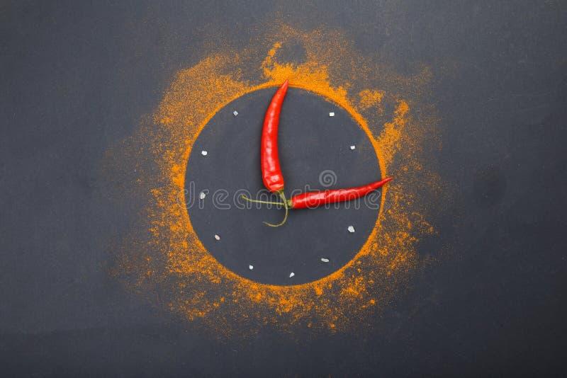 Composizione di un orologio dalle spezie e dai peperoncini su un fondo nero immagine stock