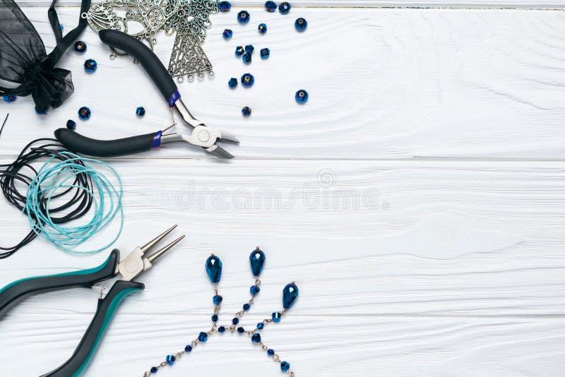 Composizione fatta a mano nel mestiere di risultati dei gioielli con gli abbellimenti delle perle delle pinze e collana su fondo  fotografie stock libere da diritti