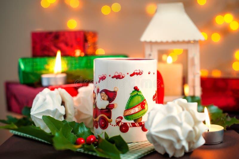 Composizione festiva in Natale - una tazza con Santa Klais, i dolci, le candele, i rami di agrifoglio, le bacche ed i regali dell immagini stock libere da diritti
