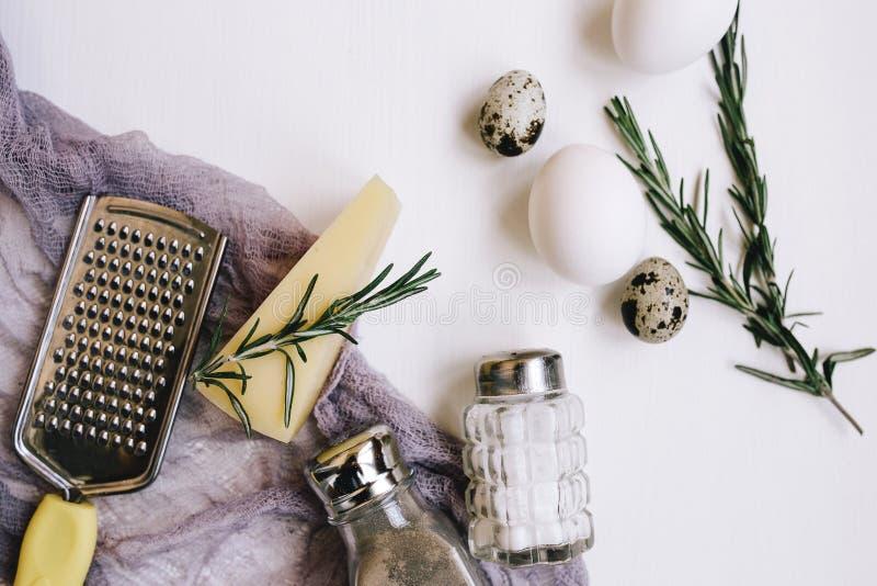 Composizione in Flatlay Formaggio a pasta dura del parmigiano con i rosmarini, saliera e pepe di vetro, uova e quaglia bianca del fotografia stock libera da diritti