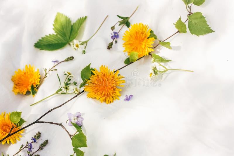 Composizione floreale fatta delle foglie e dei fiori sul fondo del tessuto fotografie stock libere da diritti